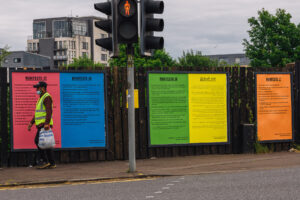 Man in hi-vis vest wearing a face mask walking past 5 largemanifesto posters that are displayed on billboards in Pollokshields Glasgow. The manifestos were made by local communities.